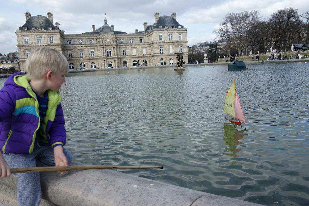 Sailing a toy boat on the Luxembourg Gardens' pond in Paris