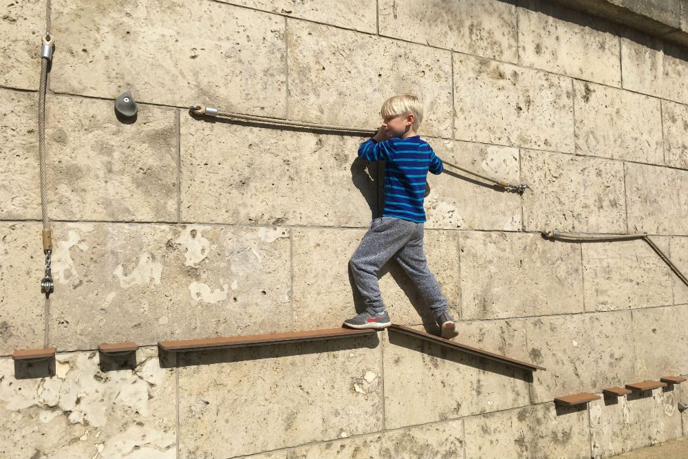 child navigates a via ferrata, one of many children's play places scattered along the banks of the Seine in Paris