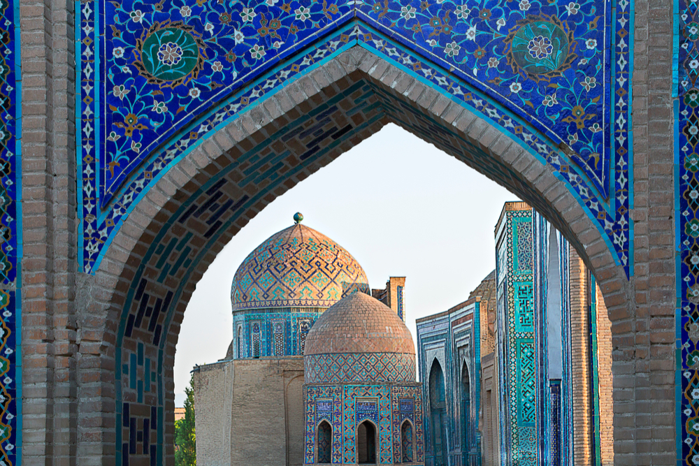 View over the mausoleums and domes of the historical cemetery of Shahi Zinda through an arched gate, Samarkand, Uzbekistan.