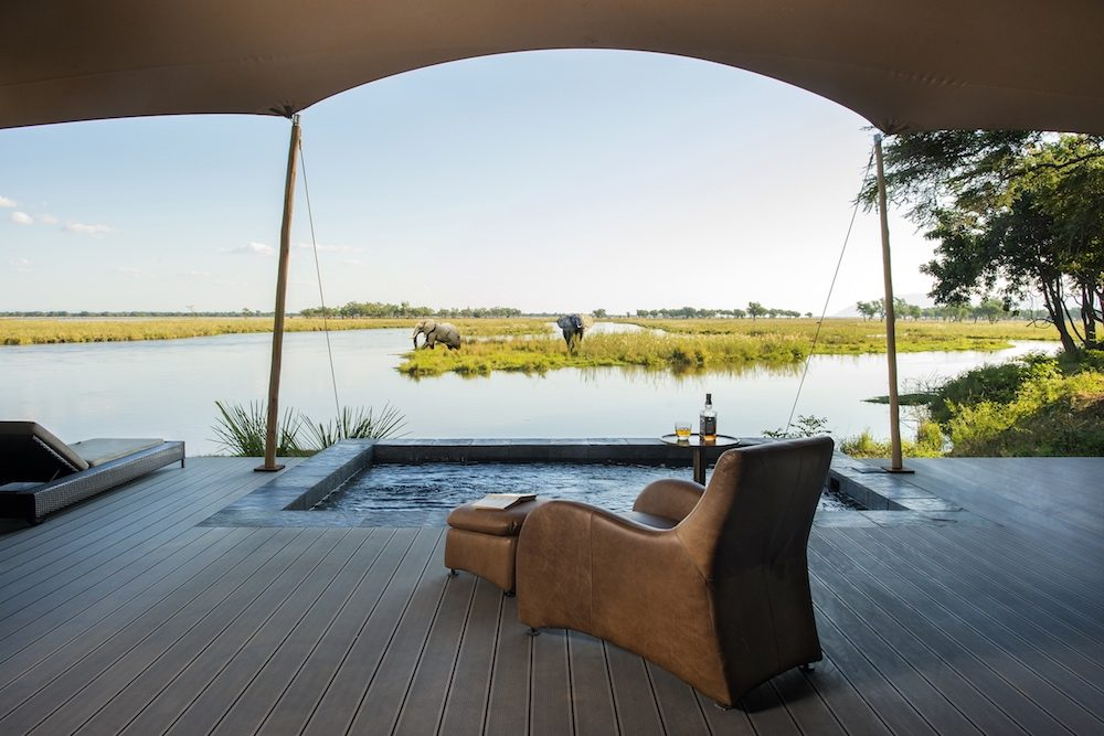 Lounge chair at Sausage Tree Safari camp in Zambia overlooking pool and watering hole and elephants on safari