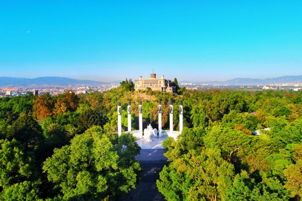 aerial view of Chapultepec Park and the Chapultepec castle in Mexico City, with green trees in foreground and city on the horizon