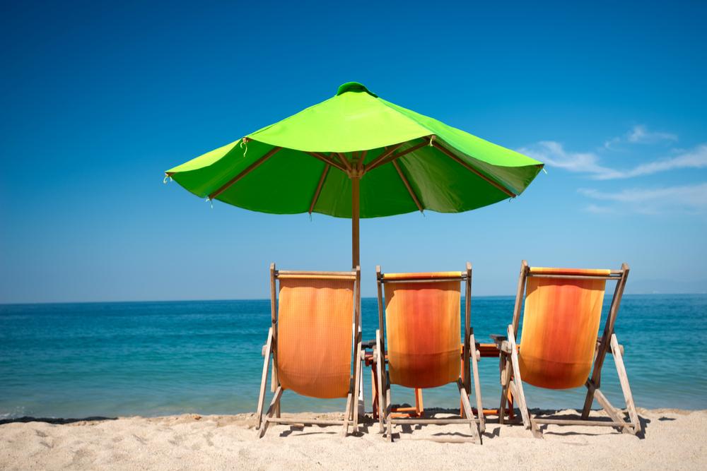 three orange beach chairs and a green umbrella facing the ocean in Puerto Vallarta Mexico