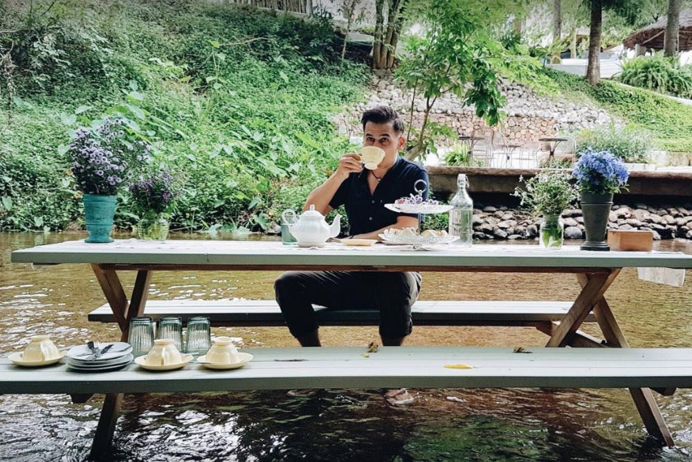 Daniel Fraser having a picnic at a picnic table in the Bangkok River Thailand