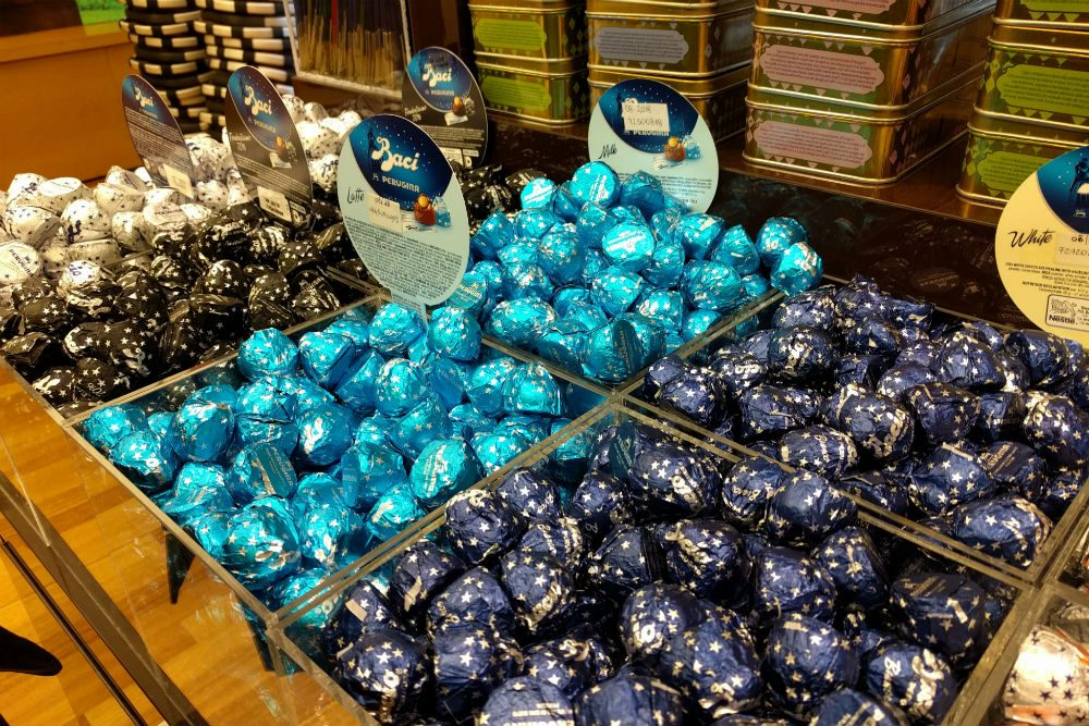 piles of Baci chocolate kisses in bins at the Perugina chocolate factory in Perugia Italy
