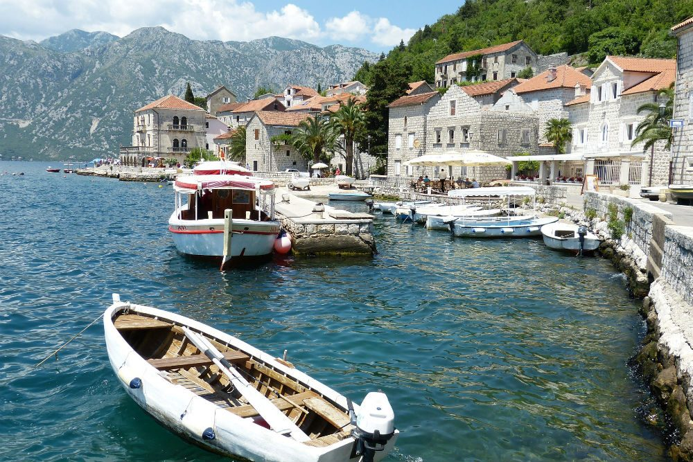 coast of Kotor Montenegro village with boats water and mountains