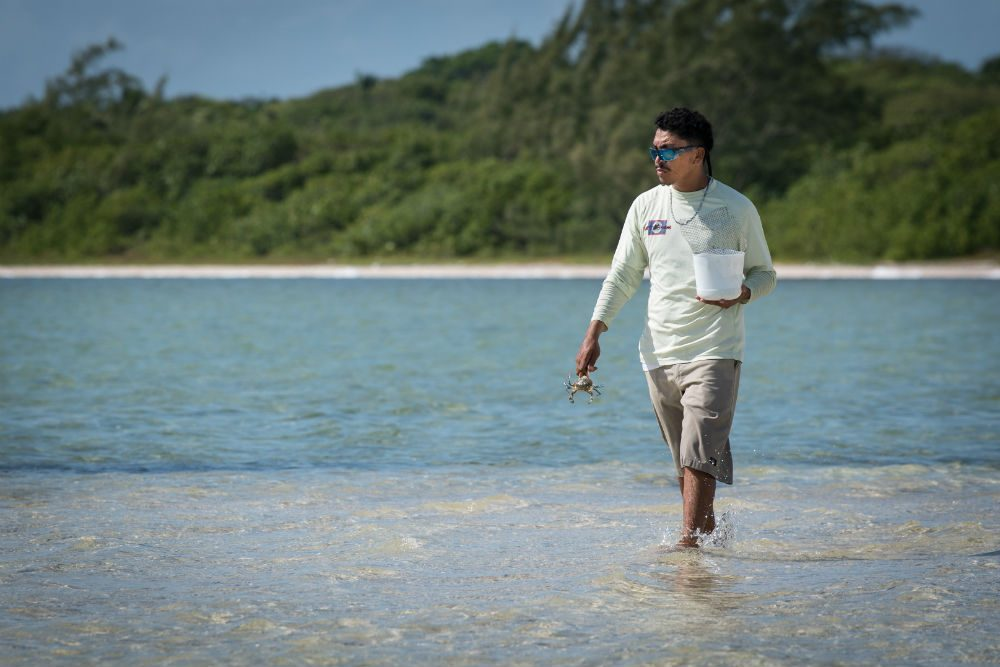 Belize fishing guide looking for crabs for bait on the beach