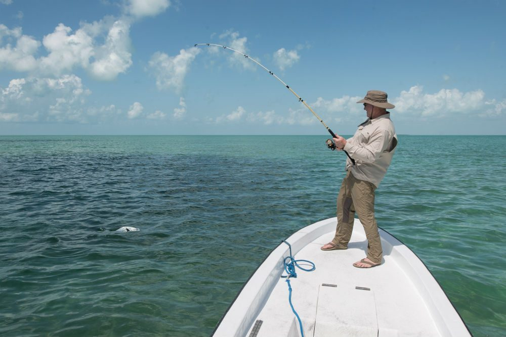 tourist fishing in Belize on a casting boat on the turquoise water