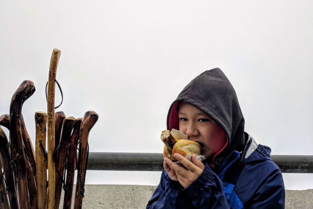 boy eating bratwurst in Bavaria with clouds behind him