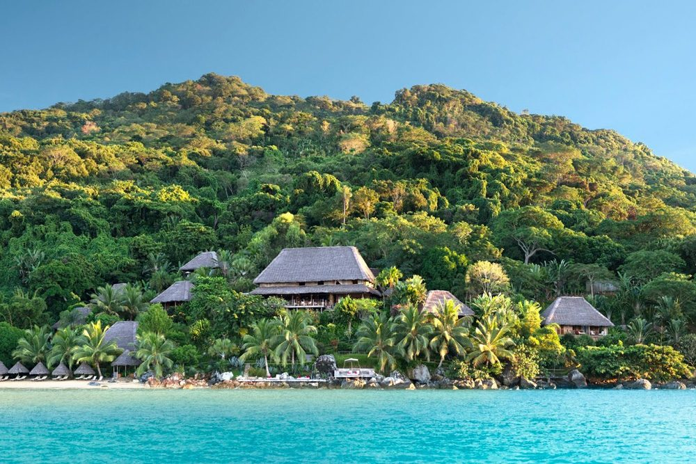 Tsara Komba resort of villas on a green hill with blue turquoise ocean in front in Madagascar
