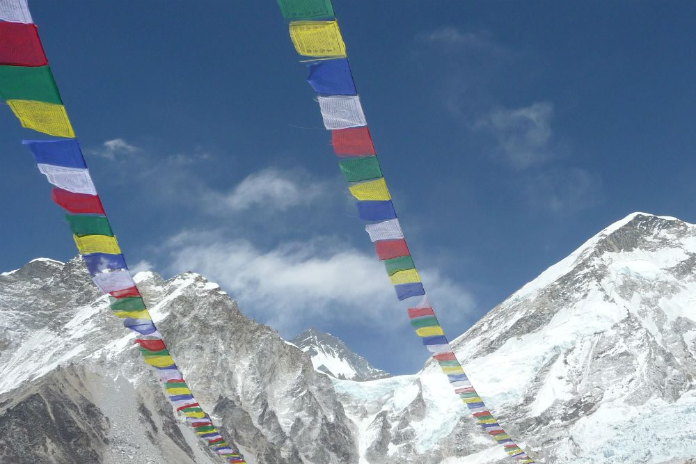 Prayer flags flying over Everest base camp with snowy himalayan mountains in background, Nepal