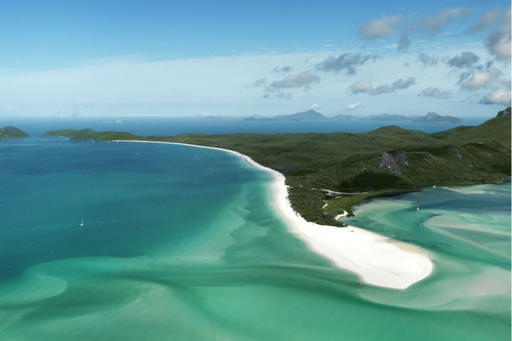 aerial photo of white-sand whitehaven beach and green mountains and turquoise sea of Whitsunday Island in Australia