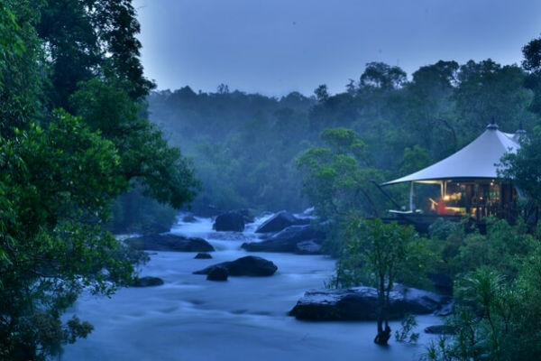 a tented safari lodge in Cambodia overlooking jungle and river