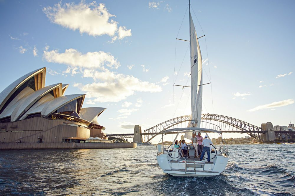 boat sailing in water on Sydney Harbour Australia with famous bridge in background