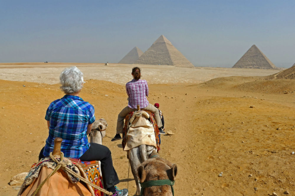 two tourists Riding camels to the pyramids in Egypt