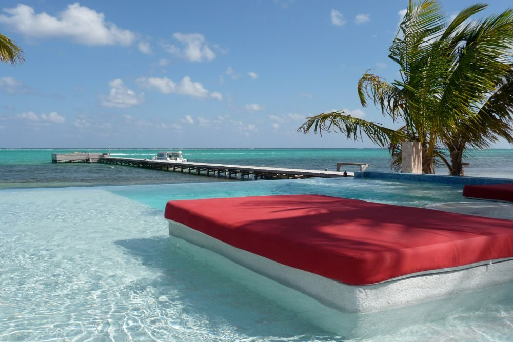 red couch in clear turquoise water at Rojo Beach Bar in Belize
