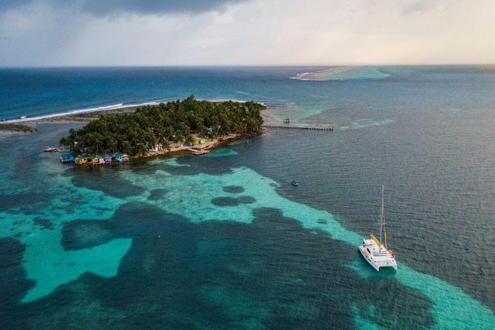 aerial photo of Tobacco Caye with sailboat and blue green ocean