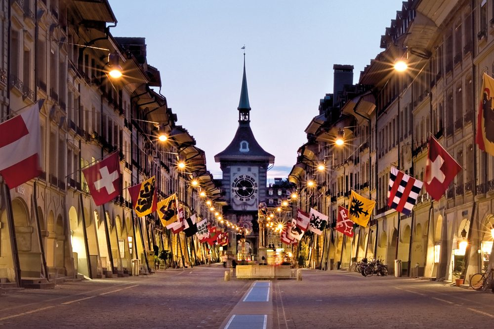 Bern Switzerland main street with lights, flags and famous clock tower