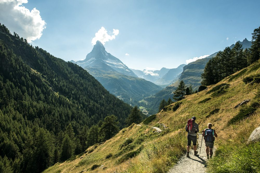 Couple at hiking in the area of Zermatt with the Matterhorn in the background.