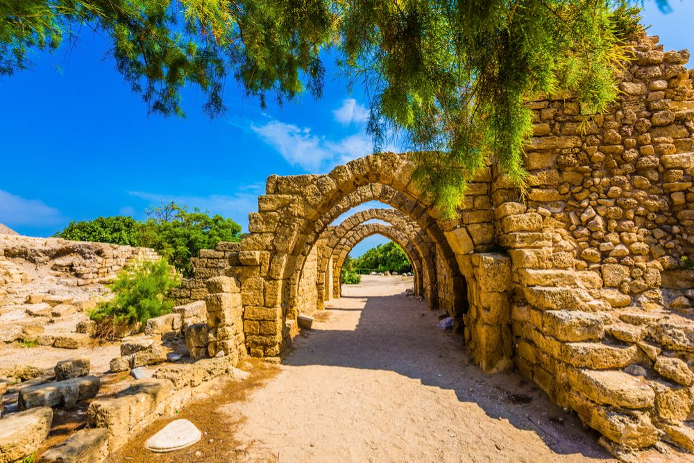 Sunny spring day. Arched passage - covered street. Picturesque ruins of the ancient seaport Caesarea. Israel.