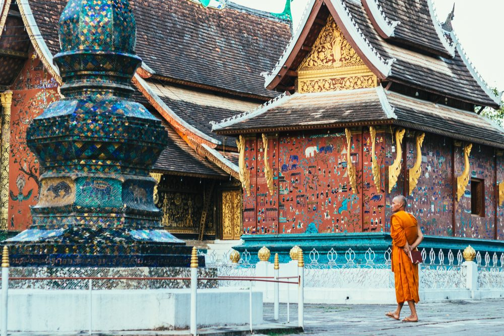 Luang Prabang, Laos - 26 November 2016: Buddhist monk and the details of architecture of Buddhist temple Wat Xieng Thong in Luang Prabang - UNESCO World Heritage Site