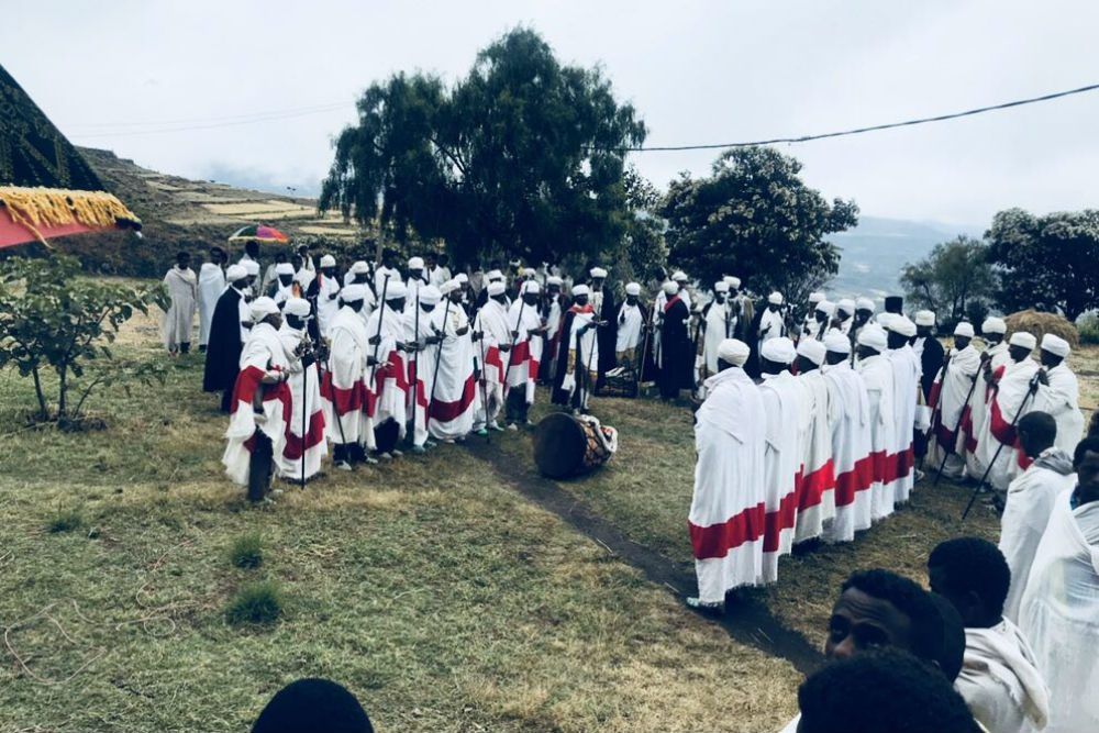 ethiopian church ceremony with many priests gathered outside by trees singing