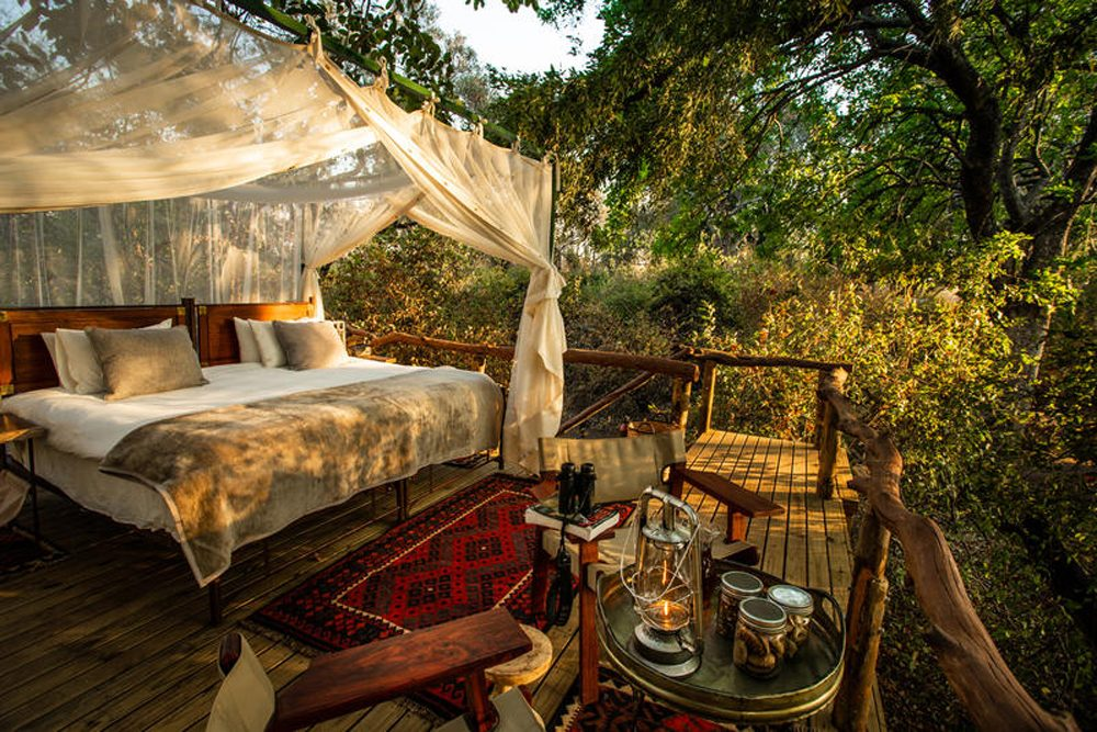 outdoor bedroom at safari lodge Sapi Explorers Camp in Zimbabwe