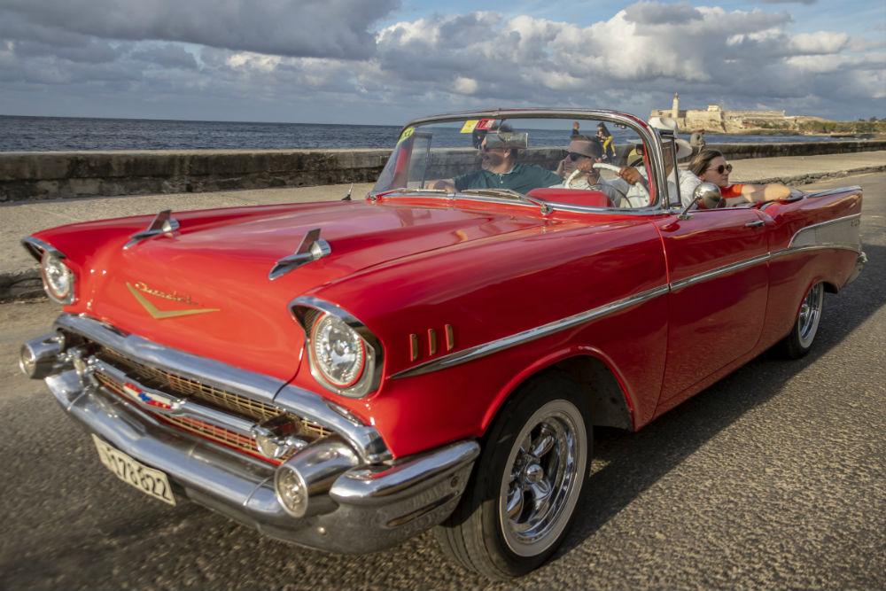 family in a red vintage car in Cuba