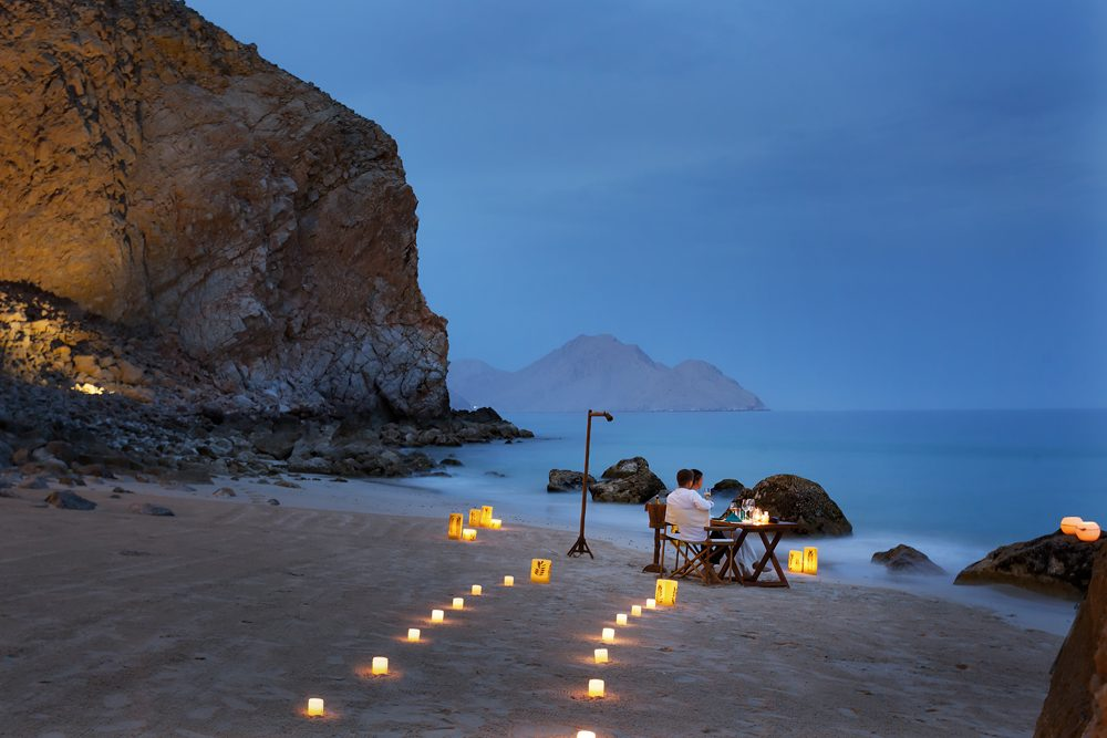 couple eating on the beach at sunset at Six Senses Zighy Bay Oman