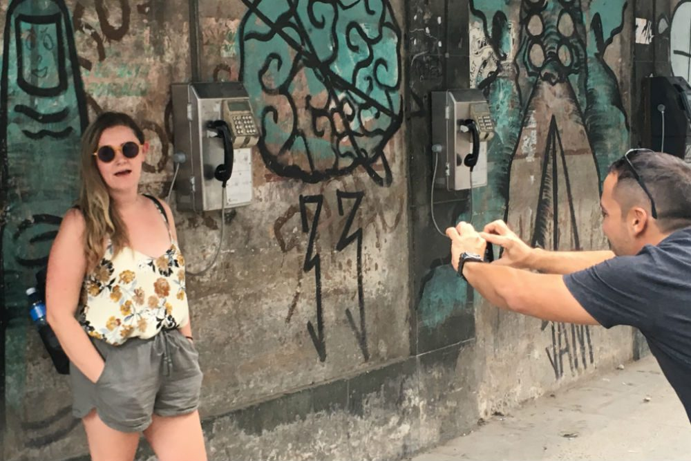 Cuban photographer Ramses Batista photographs a tourist against a wall with street art