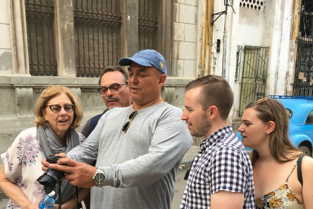 Photographer Alex Castro shows a tourist family how to take photos in Cuba
