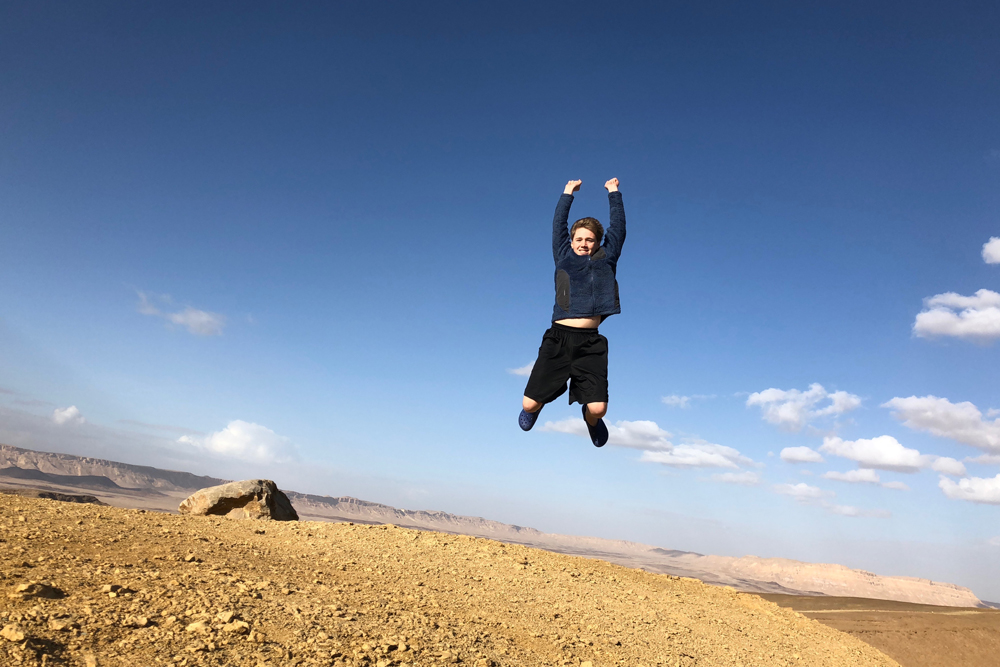 teenage boy jumping in Negev Desert Israel