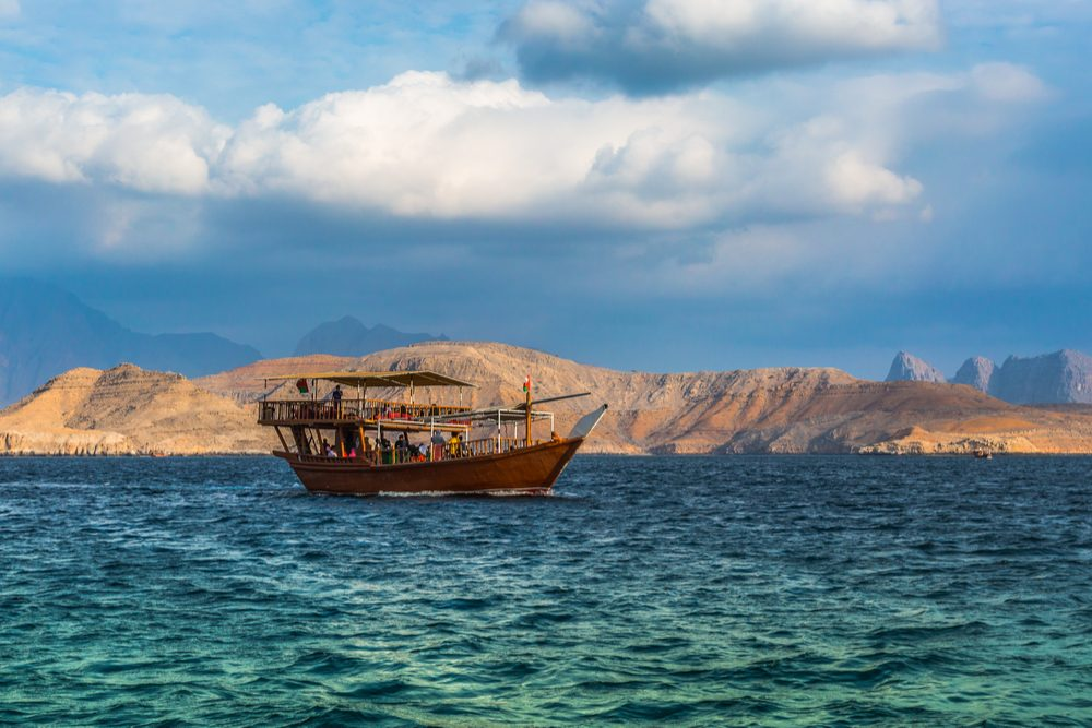 Dhow boat Cruise in Arabian Peninsula, boat on blue water with desert mountains in background