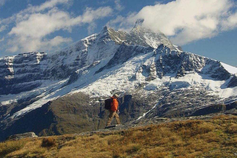 Mount Aspiring New Zealand with snow on mountain and hiker walking in foreground