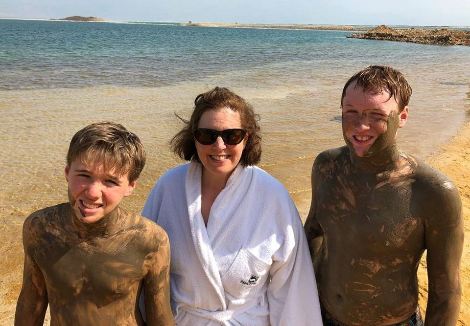 a mom and two sons covered in mud at the Dead Sea