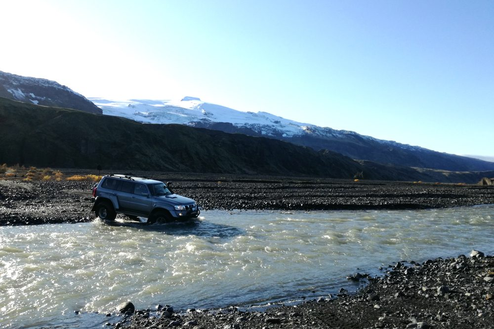 A super jeep crosses a river in Thorsmork Valley.
