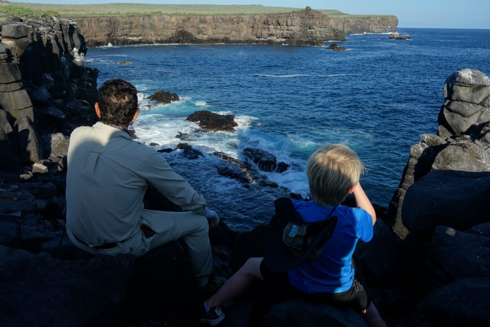 Galapagos Cruise boy spotting seabirds off coast