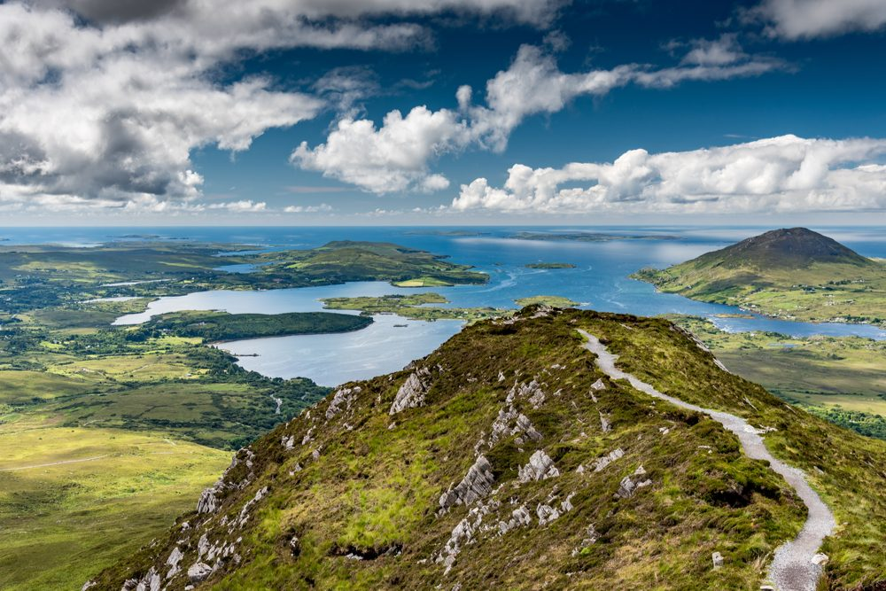 The hiking trail at the top of Diamond Hill in Connemara National Park, Ireland. Behind, the sun plays with the clouds reflected in the sea. - Image