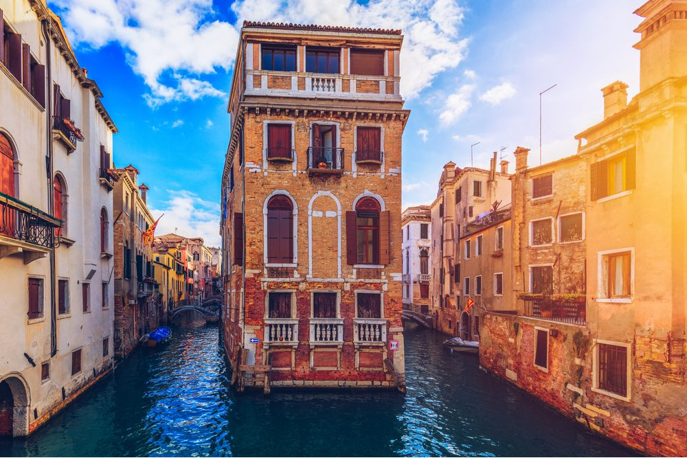 View of the street canal in Venice, Italy. Colorful facades of old Venice houses. Venice is a popular tourist destination of Europe. Venice, Italy. - Image