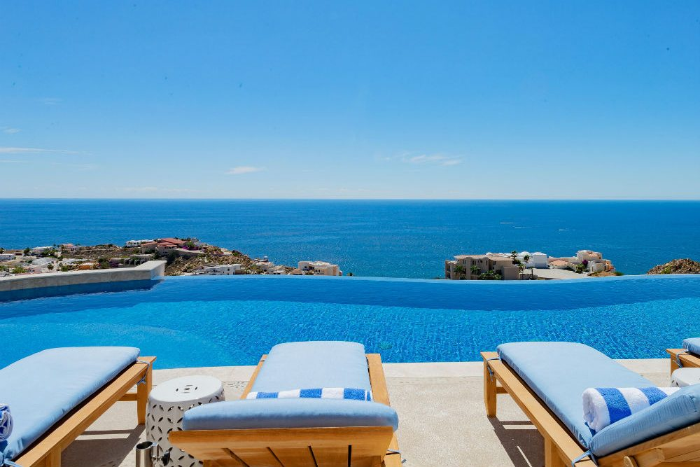 chaise lounges overlooking infinity pool and blue ocean in Cabo San Lucas Mexico