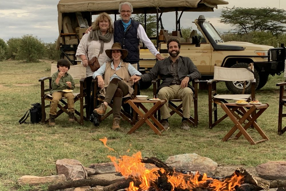multigenerational family sitting in front of a jeep and a campfire in Kenya