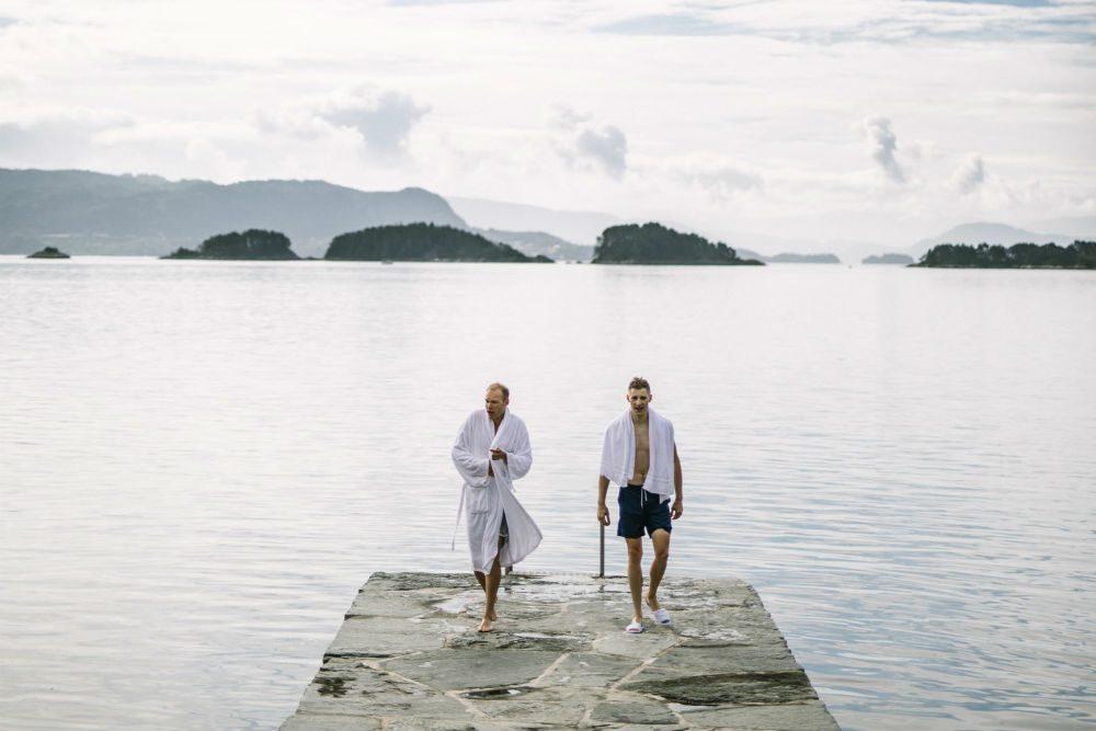 two men walking on a lake pier at Solstrand Hotel in Norway