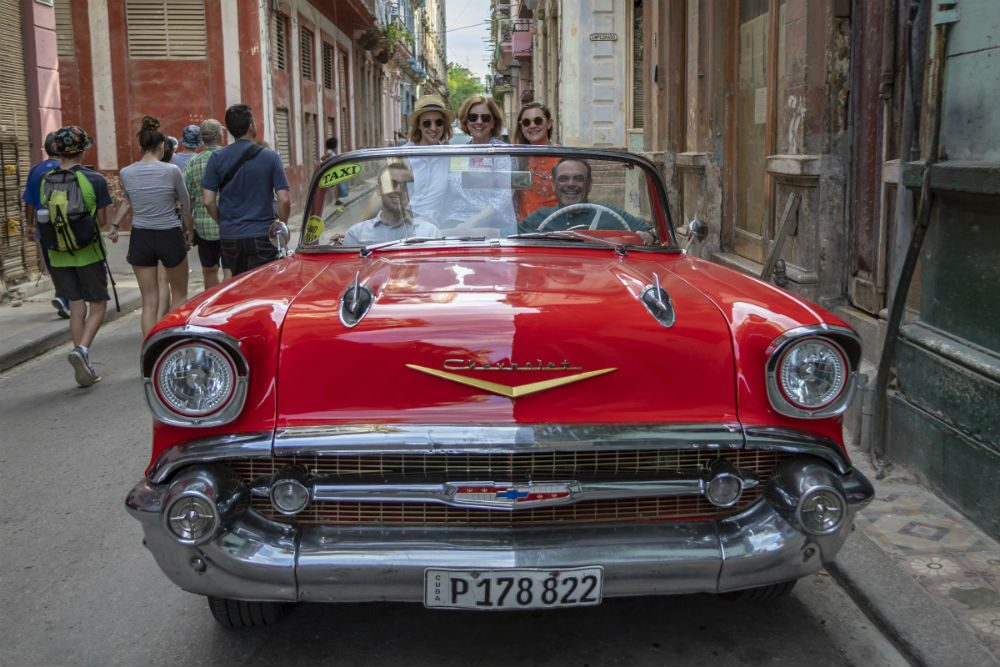 family in old fashioned red car on the streets of Havana cuba
