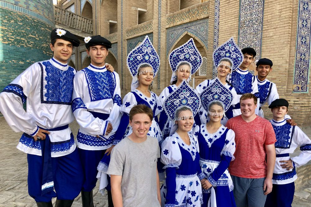 american tourists posing with dancers in traditional blue and white dress in Uzbekistan