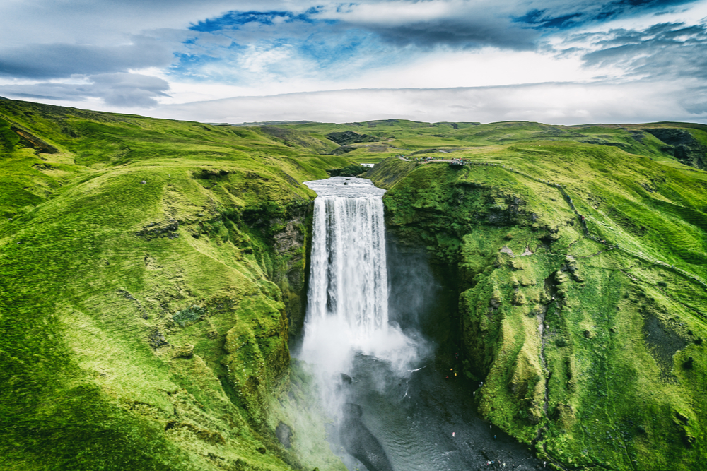 Iceland waterfall Skogafoss in Icelandic nature landscape. Famous tourist attractions and landmarks destination in Icelandic nature landscape on South Iceland. Aerial drone view of top waterfall. -