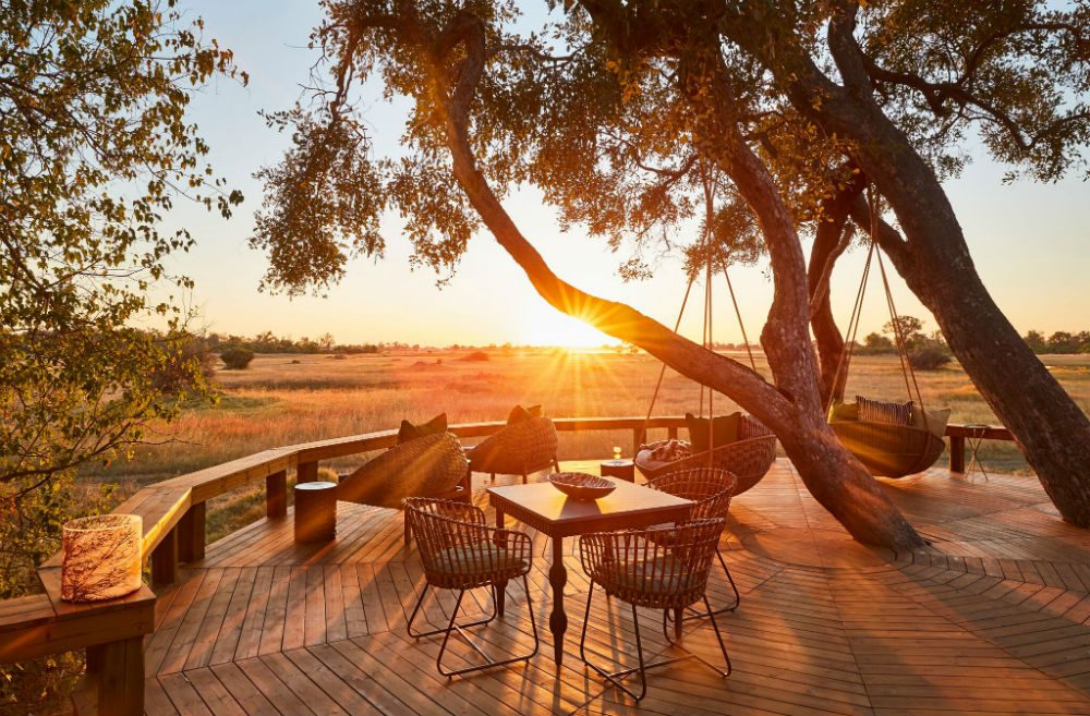 view from the deck of Tuludi safari camp in Botswana with sunset, Okavango delta and tree
