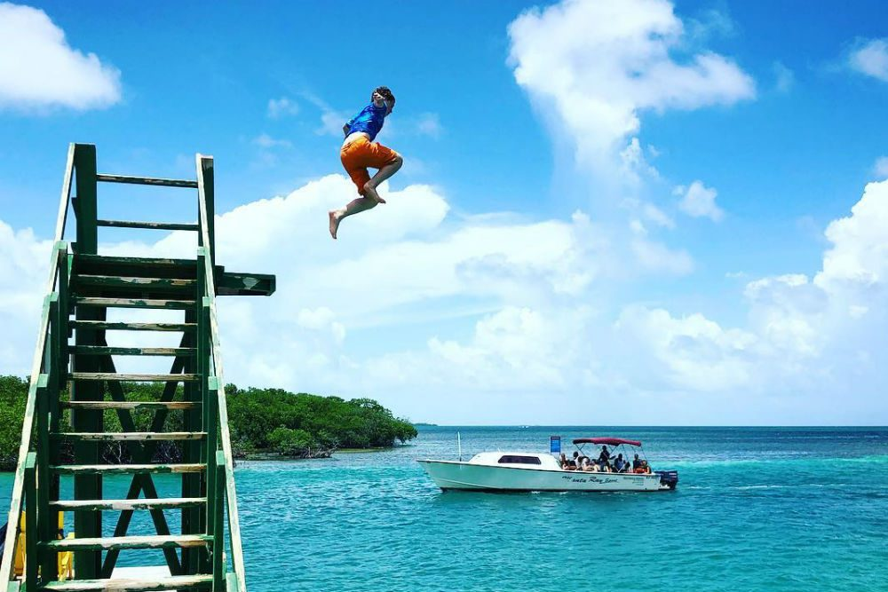 boy jumping in to ocean from a high dock in Belize