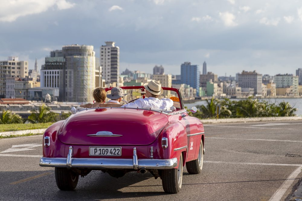 tourists riding in old fashioned red car in Cuba