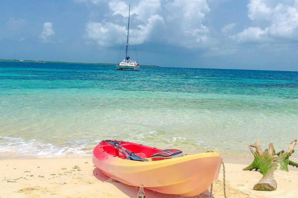 a yacht is anchored at Sergeant's Caye off the shore in Belize with yellow kayak on sand
