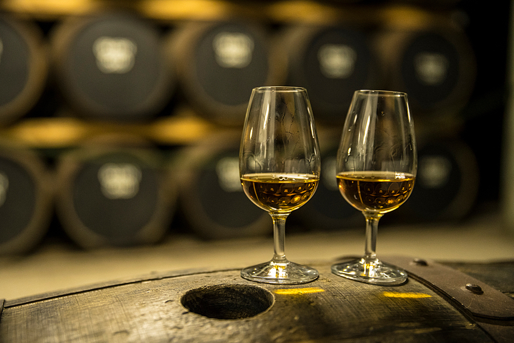 Glen Ord, the nearest distillery to Inverness and Loch Ness in the Highlands of Scotland. Two glasses of whisky standing on an oak barrel.