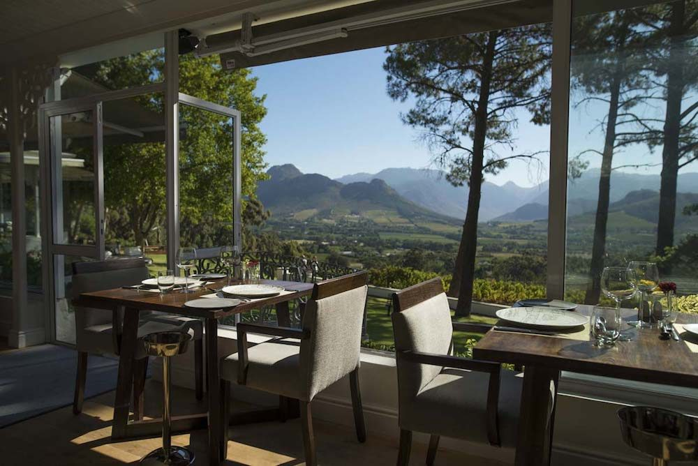 restaurant tables overlooking vineyards at Lat Petite Ferme restaurant in Franschhoek South Africa